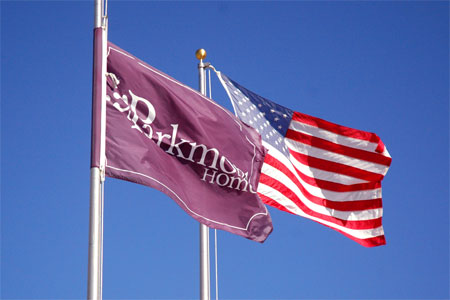 Custom Parkmont Homes flag flying with the U.S. flag