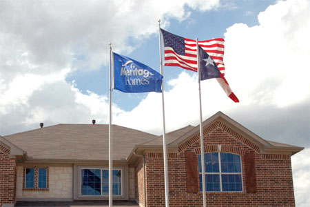 Custom Meritage Homes flag flying with the U.S. flag and Texas state flag in front of a model home