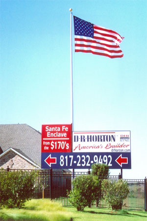 U.S. flag flying flying behind a large D. R. Horton branded sign
