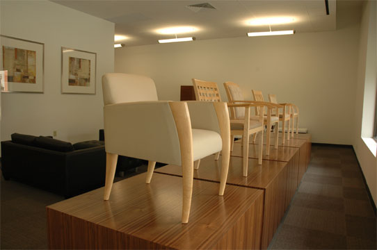 A line of guest chairs on pedestals at the entrance of the Novikoff Furniture showroom