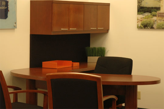A typical Novikoff Furniture Metaplan desk in a dark wood color with two guest chairs an one executive chair