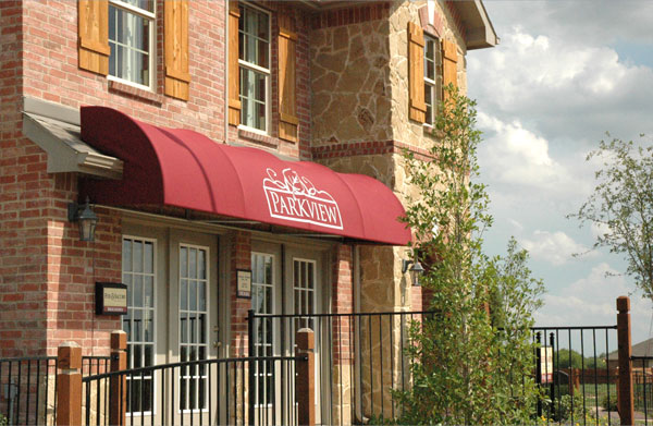 A red awning with a curved front mounted on a model home
