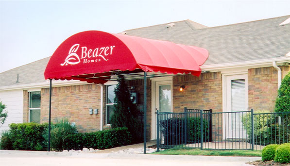 A red awning with an arched top mounted over the front door of a model home